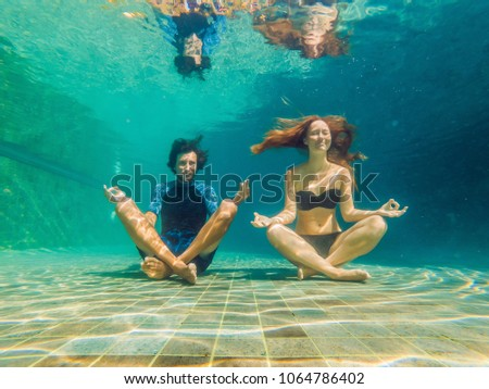 young woman in black bikini and man in yoga position underwater in diving aquarium full body shot stock photo © galitskaya