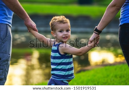 little boy and his father and mother enjoying outdoors in field of daisy flowers stock photo © lopolo