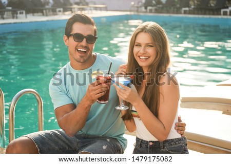 smiling couple with glasses of alcohol cocktails near swimming p stock photo © dashapetrenko