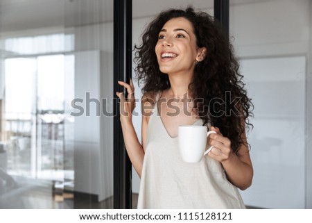 photo of pretty woman with long dark hair standing in bathroom stock photo © deandrobot