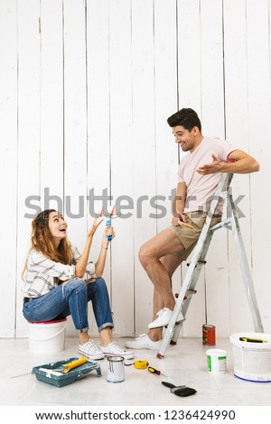 Portrait of lovely couple man and woman using ladder, while pain Stock photo © deandrobot