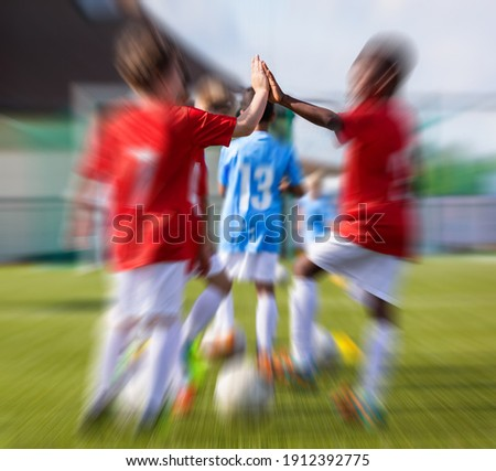 Young Sports Coach Making a High Five with Kids Player. Junior Soccer Coach Coaching Children on Spo Stock photo © matimix