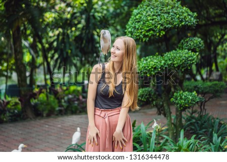Young woman feeding ibes in the park. Little Egret Cattle egret Bubulcus ibis Waters Edge. Spoiled h Stock photo © galitskaya