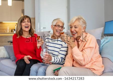 Három idős barátok fuvolák pezsgő ül Stock fotó © pressmaster