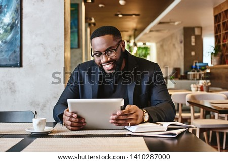 Portrait of young African-American male executive using mobile phone in modern office. Diverse execu Stock photo © wavebreak_media