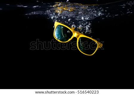 Yellow sunglasses splashing into water on black background. eyewear falling into water. Copy space. Stock photo © Illia