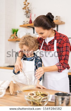Young mother teaching little son how to shake raw eggs in bowl in the kitchen Stock photo © pressmaster