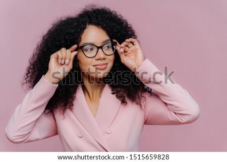 Headshot of attentive female boss keeps hands on frame of glasses, looks pensively away, wears rosy  Stock photo © vkstudio