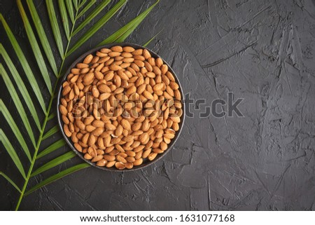 Composition of Whole almond nuts in black plate placed on black stone table Stock photo © dash