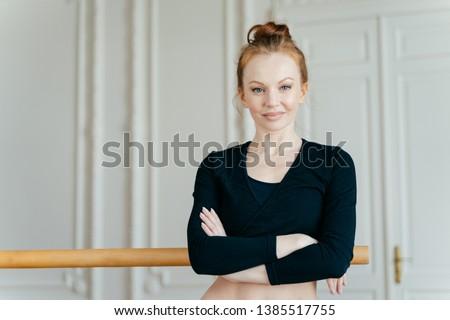 Waist up shot of satisfied self confident ballet dancer crosses hands over chest, wears black top, h Stock photo © vkstudio