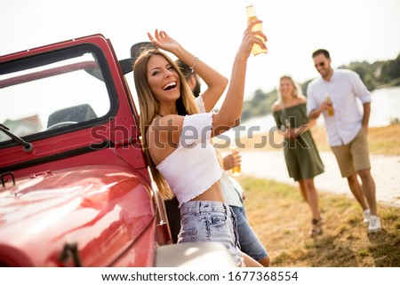 Two happy young women drinking cider by the vehicle on the lakes Stock photo © boggy