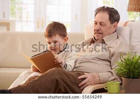 old man sitting in the armchair with his grandchild standing bes Stock photo © meinzahn