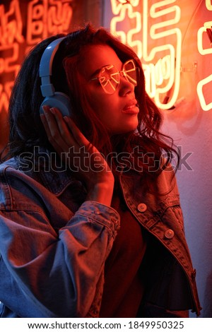 Vertical image of Woman standing near the Illuminated signboard Stock photo © deandrobot