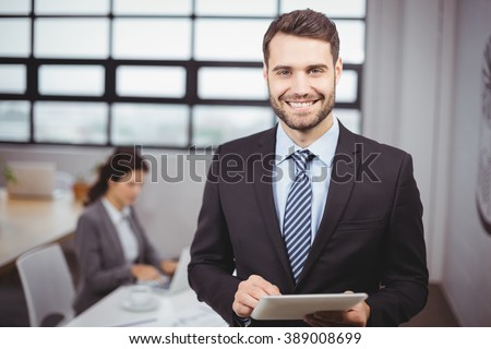 businessman using digital tablet while female colleague analyzing documents stock photo © wavebreak_media