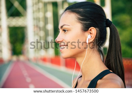 side view of happy sportswoman in headphones running with smartphone stock photo © deandrobot