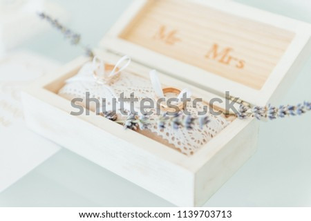 Side view shot of two gold wedding rings on flowers in old rustic wooden box for wedding ceremony. stock photo © ruslanshramko