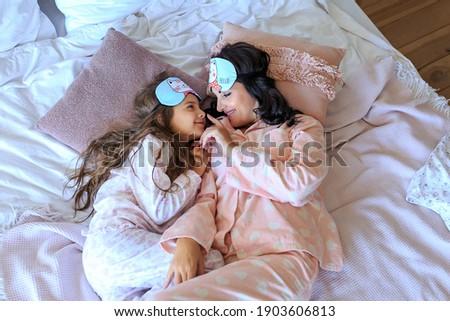 two cheerful girls in masks for sleeping have fun playing sleepwalking Stock photo © ruslanshramko
