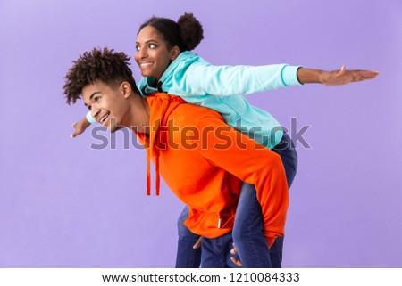 Photo of beautiful african american guy piggybacking his girlfri Stock photo © deandrobot