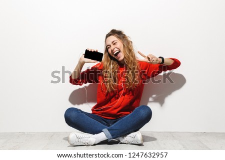 photo of funny woman 20s singing and holding mobile phone while stock photo © deandrobot