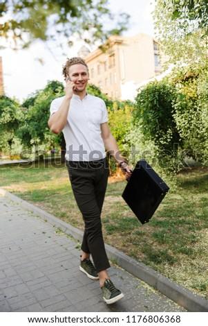 Zufrieden lockig Geschäftsmann Aktentasche sprechen Smartphone Stock foto © deandrobot