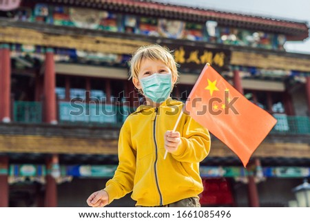 Enjoying vacation in China. Young boy with national chinese flag on the background of the old Chines Stock photo © galitskaya