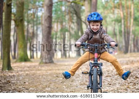 happy kid boy of 5 years having fun in the park with a bicycle o stock photo © galitskaya