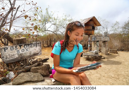 Post Office Bay - tourist looking at postcards on Floreana Galapagos Islands Stock photo © Maridav