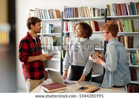 Group of young casual classmates discussing their ideas in library Stock photo © pressmaster