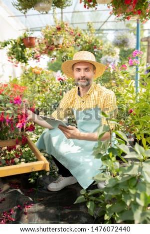 Tijdgenoot landbouwer werkkleding zoeken nieuwe bloemen Stockfoto © pressmaster