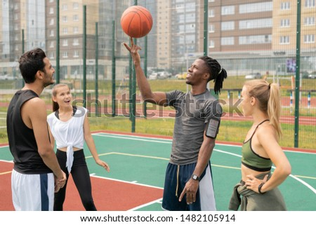 Happy young African sportsman holding ball on forefinger among friends Stock photo © pressmaster