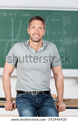 Front view of a handsome Caucasian male teacher teaching a mixed-race schoolboy to draw in a classro Stock photo © wavebreak_media