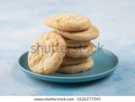 White chocolate biscuit cookies on blue ceramic plate with tea pot and cup on blue kitchen table bac Stock photo © DenisMArt