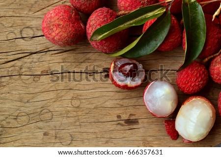 fresh organic lychee fruit and lychee leaves on a rustic wooden background stock photo © galitskaya