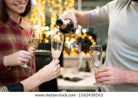 Hands of young businesspeople with flutes going to have champagne for xmas Stock photo © pressmaster