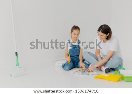 Small girl and her mother sit on floor, look attentively at color palette, choose best colour for pa Stock photo © vkstudio