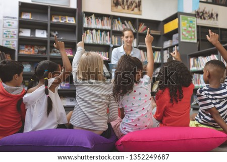 Rear view of school kids sitting on big colored cushions raising hand to answer at a question asking Stock photo © wavebreak_media