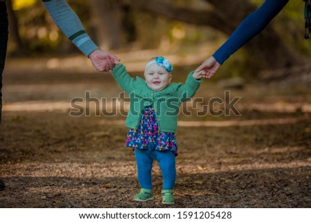 Outdoors small breasted girl 1 year of age holding parents hand and smiling Stock photo © ElenaBatkova