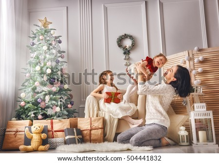 Happy mom celebrates Christmas with her daughter. Mom and daughter are dressed in red skirts and the Stock photo © ElenaBatkova