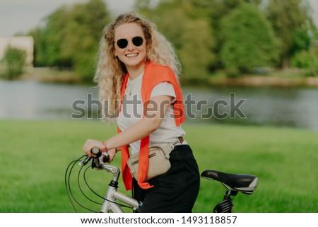 Pretty female bike rider stops near beautiful river, wears sunglasses, white t shirt, jumper on shou Stock photo © vkstudio