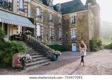 Pleasant looking female wears mantlet and trousers stands against big brick ancient builduing or cas Stock photo © vkstudio
