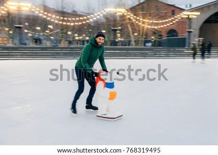 Photo of male skater keeps balance on skate ring, stands on skat Stock photo © vkstudio