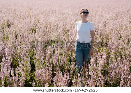 Portrait of beautiful young woman posing in sage field in summer sun Stock photo © GVS