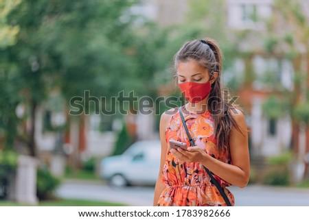 COVID-19 Mandatory mask wear in city Woman walking wearing mask protection as prevention for coronav Stock photo © Maridav
