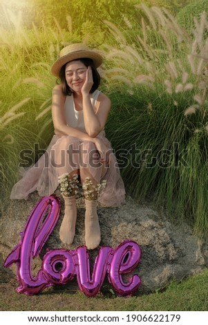 beautiful woman peacefully smilling surrounded by flower petals with a flower on her ear stock photo © wavebreak_media