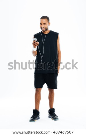 Full-length portrait of a happy sports man standing over white background Stock photo © deandrobot