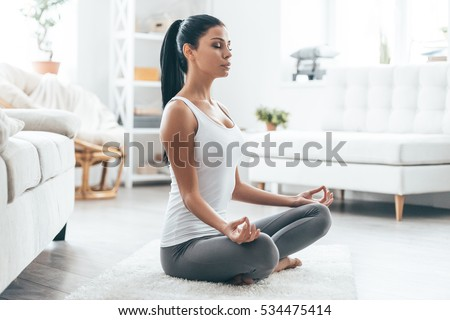 Attractive young woman meditating while sitting in lotus pose Stock photo © deandrobot