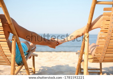 Couple holding hands while relaxing on lounge chairs at beach Stock photo © wavebreak_media