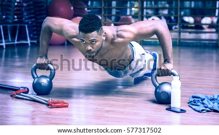 Portrait of a fit muscular afro american sportsman doing plank Stock photo © deandrobot