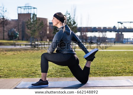 Young woman stretching her quadriceps muscles by grabbing her ankle Stock photo © Kzenon
