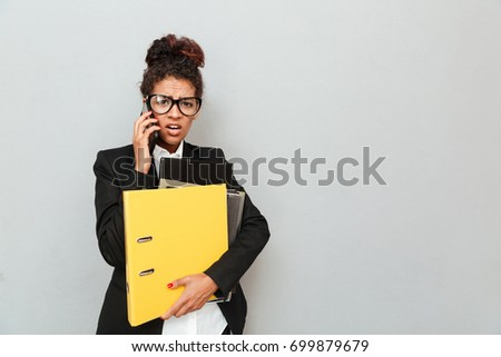 shocked business woman standing over grey wall background with speech bubbles chatting by mobile pho stock photo © deandrobot
